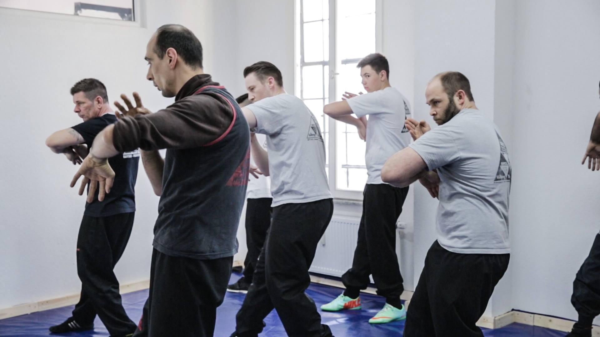 Gruppe Männer trainiert zusammen Escrima