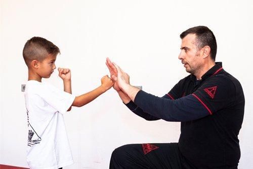 Sifu Spyros Dovridis zeigt Kind wie man abblockt